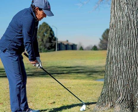 Elena King hits shot next to tree left-handed